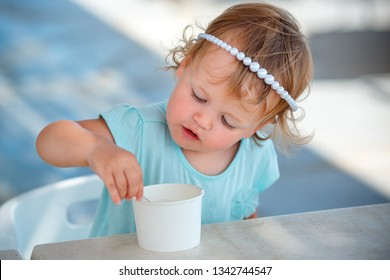 Adorable little girl eating ice cream at outdoor cafe on beautiful summer day