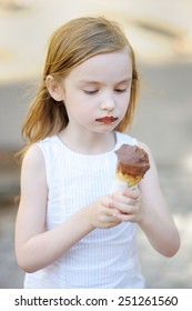 Adorable little girl eating ice cream outdoors at summer