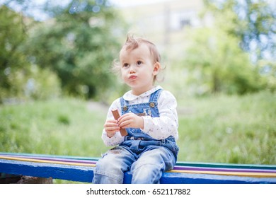 Adorable little girl eating milk chocolate outdoors on warm and sunny summer day