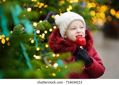 Adorable little girl eating red apple covered with sugar icing on traditional Christmas market. Child enjoying sweets, candies and gingerbread on magical Xmas time.