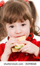 Adorable little girl eating sandwich