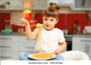Adorable little girl eating spaghetti sitting on table