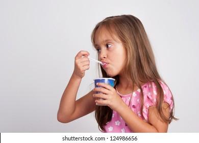 Adorable Little Girl Eating Yogurt