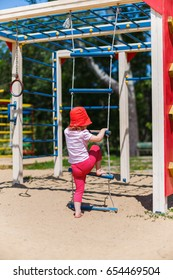 Adorable little girl enjoying her time in climbing adventure park on warm and sunny summer day.  Child having fun on school vacations. A little girl in red panama walks barefoot