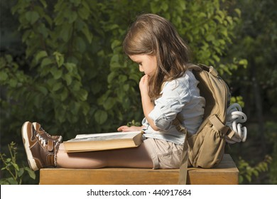 Adorable little girl in explorer clothes reading old book sitting in a wooden suitcase with backpack and safety rope outdoor. Children's play concept