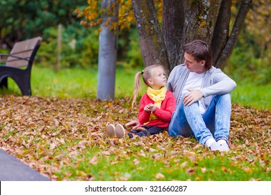 Adorable little girl with father in beautiful autumn park outdoors