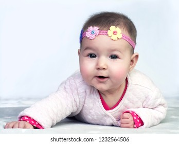 Adorable little girl with flowers in the hair on the grey background. Portrait of the babbling 4 month small baby.