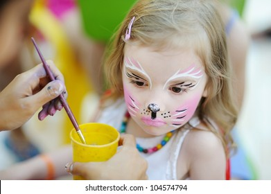 Adorable little girl getting her face painted