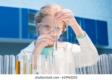 adorable little girl in goggles with reagents in tubes in laboratory