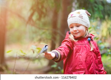 Adorable little girl and great tit bird sitting on her finger