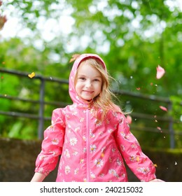 Adorable little girl happily standing under the rain on autumn day