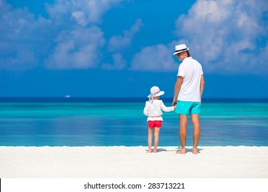 Adorable little girl and happy father during tropical beach vacation