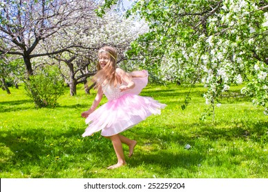 Adorable little girl have fun in blossoming apple tree garden