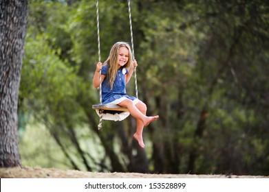 Adorable little girl having fun on a swing outdoor