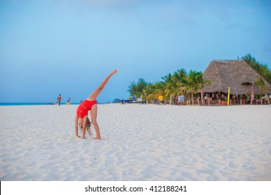 Adorable little girl having fun making cartwheel on tropical beach at sunset