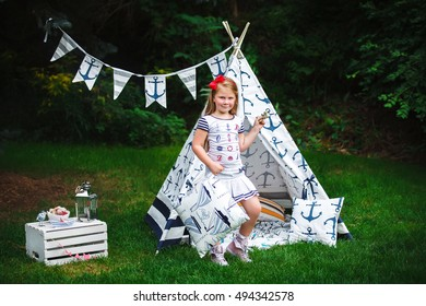 Adorable little girl having fun playing outdoors on summer day with sea style teepee