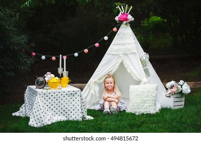 Adorable little girl having fun playing outdoors on summer day with teepee