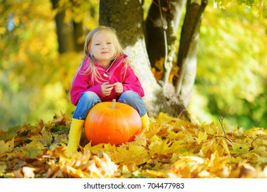 Adorable Little Girl Having Fun On A Pumpkin Patch On Beautiful Autumn Day  Outdoors. Happy