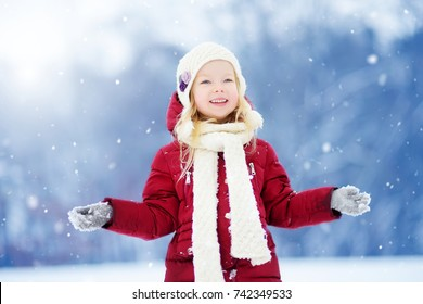Adorable little girl having fun in beautiful winter park. Cute child playing in a snow. Winter activities for kids.