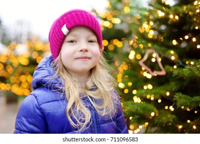 Adorable little girl having wonderful time on traditional Christmas market. Child enjoying herself near Christmas trees decorated with lights and baubles.
