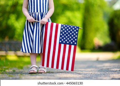 Adorable little girl holding american flag outdoors on beautiful summer day. Independence Day concept.