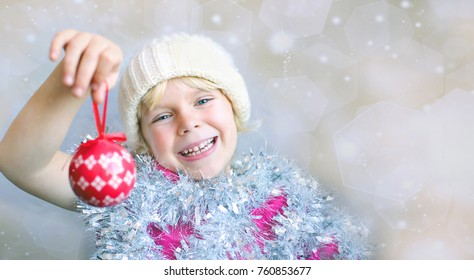 Adorable little girl holding Christmas ornament. Space for simple text