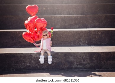 Adorable Little Girl Holding Heart Foil Balloons and a Red Rose on Valentine's Day