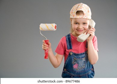 Adorable little girl holding paint roller and phone receiver