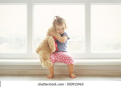 Adorable little girl hugging a teddy bear. Cute baby at home in white room is sitting near window.