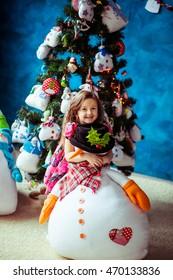 Adorable little girl hugs toy snowman