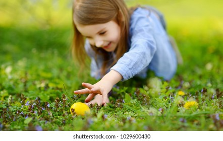 Adorable little girl hunting for Easter eggs in blooming spring garden on Easter day. Cute child celebrating Easter outdoors.