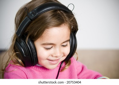 adorable little girl listening to music through headphones