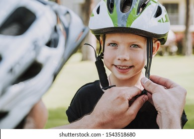 Adorable little girl looking at camera and smiling while dad fastening her helmet for safety