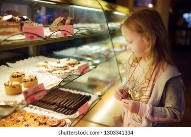 Adorable little girl looking at fresh baked cookies on display in small store in Vilnius, Lithuania. Child choosing a dessert. Sweets for kids.
