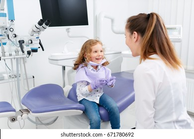 Adorable little girl looking into medic mouth while playing a doctor with female pediatric dentist in cabinet. Dentist and child in cabinet. Dentist office. Little girl in the dentists office