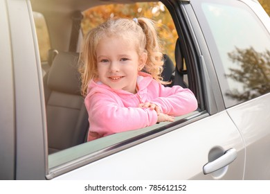 Adorable little girl looking out of car window
