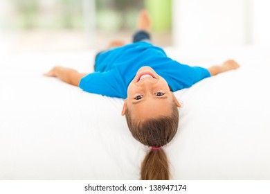 adorable little girl lying on bed at home