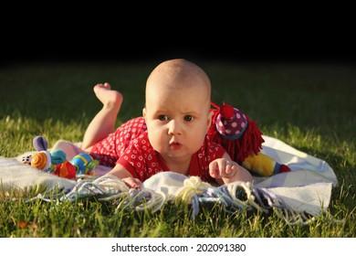 Adorable little girl lying on green grass in sunlight