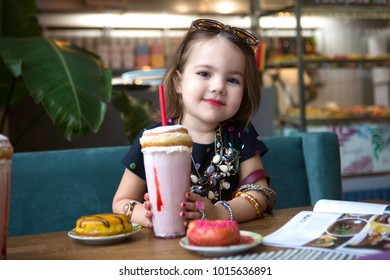 Adorable little girl with milkshake and dessert  in a cafe. The child sits at a table in a cafe. little girl as adult. children imitate adults.