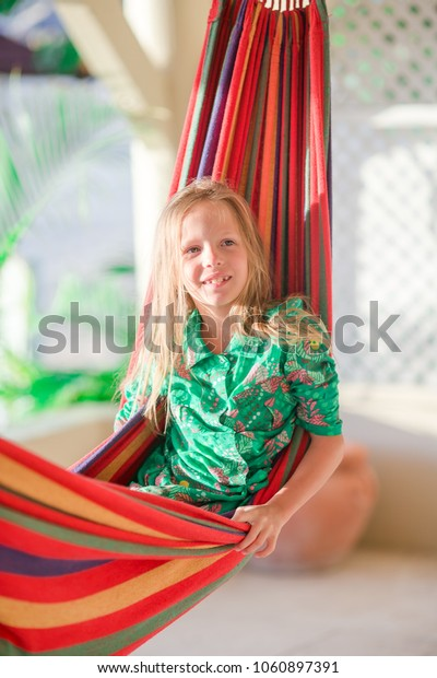 Adorable little girl on summer vacation sleeping in hammock