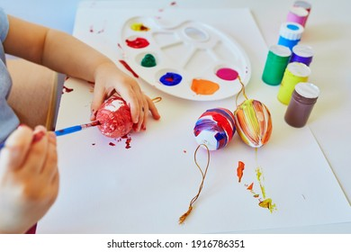 Adorable little girl painting eggs for Easter at home, in kindergaten or preschool. Celebrating holidays with children. Creative activities and games for kids. Stay at home entertainment
