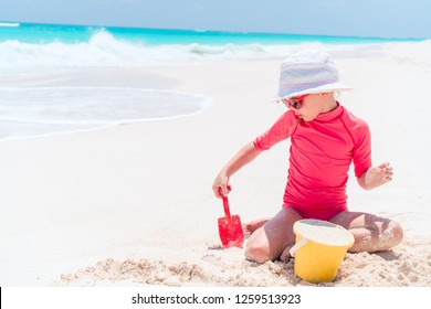 Adorable little girl playing with beach toys and sand making a sandcastle on beach vacation
