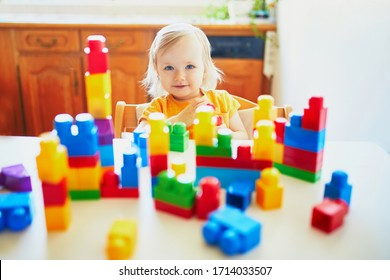 Adorable little girl playing with colorful plastic construction blocks at home, in kindergaten or preschool. Creative games and staying at home entertainment for kids