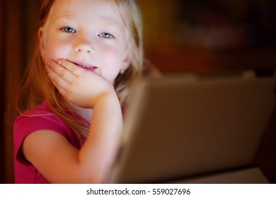 Adorable little girl playing with a digital tablet in a dark room. Child in an elementary school. Education and learning for kids.