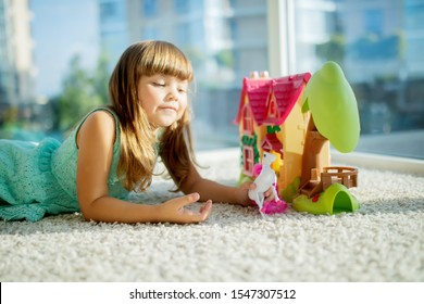 Adorable little girl playing with a dollhouse while sitting on the floor