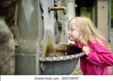 Adorable little girl playing with drinking water fountain in Lindau, Germany