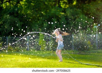 Adorable little girl playing with a garden hose on hot and sunny summer evening