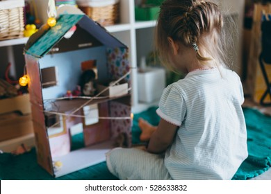 Adorable little girl playing with a hand made card-box doll house