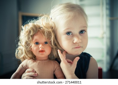 Adorable little girl playing in her room with doll. Toned image.