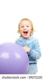 Adorable  little girl playing with a large rubber  purple fitness ball on the floor.